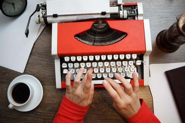 Máquina de escribir vintage roja con papel en blanco