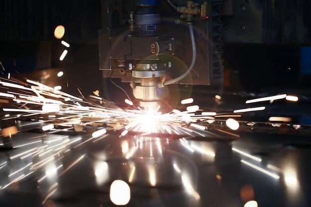 Máquina láser de corte por metal. volar fuego chispas de fondo.