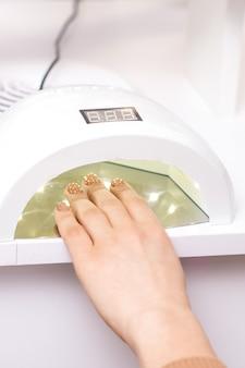 Máquina de manicura con esmalte de gel de lámpara uv durante el proceso de secado de uñas en un salón de belleza