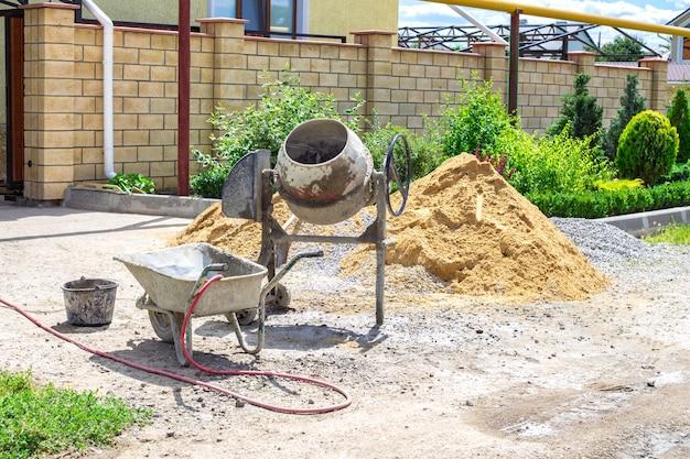 Máquina mezcladora de cemento en obra, herramientas y arena.