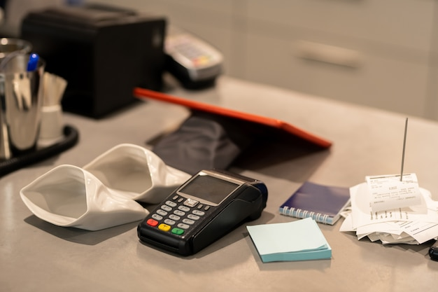 Máquina de pago electrónico, dos pequeños sacos vacíos para cambio, papel de notas y pila de recibos en el lugar de trabajo del contador