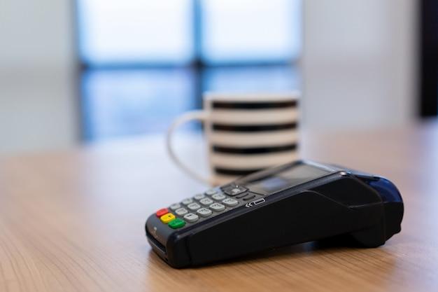 Máquina de pago con tarjeta de crédito en mesa con taza de café blanco en mesa en la cafetería