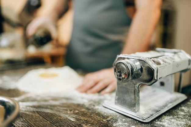 Máquina de pasta, chef masculino preparando masa en la mesa de la cocina de madera. cocinar espaguetis caseros