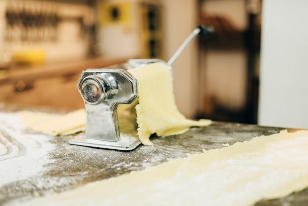 Máquina de pasta con masa en la mesa de la cocina de madera