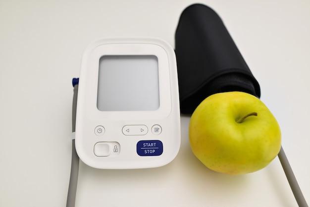 Máquina de presión arterial y una manzana roja.