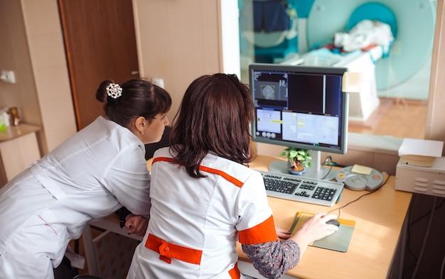 Máquina de resonancia magnética y pantallas con médico y enfermera