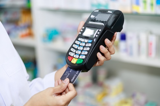 Máquina de tarjetas de crédito en la mano femenina farmacéuticas en la tienda de farmacia tailandia