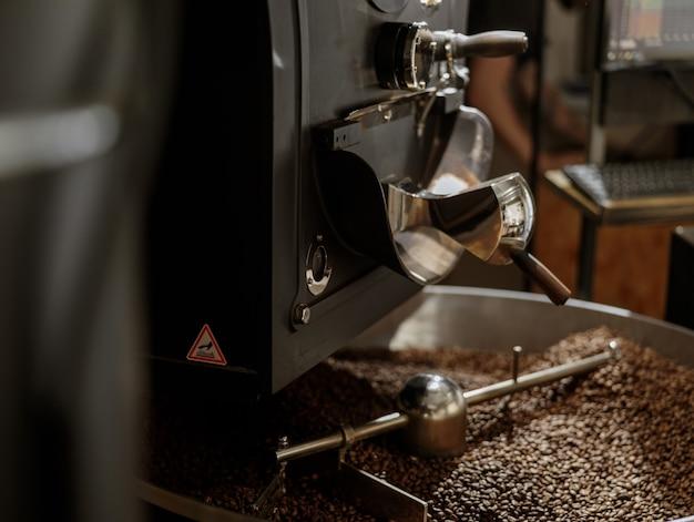 Máquina tostadora de café con granos de café en bandeja de enfriamiento