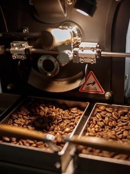 Máquina tostadora industrial con granos de café marrón