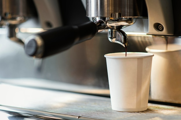 Máquina vertiendo café en vaso desechable