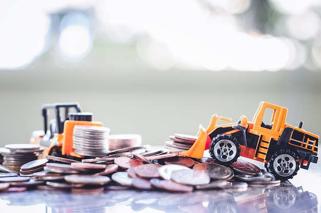 La maquinaria pesada del juguete amarillo con la pila de monedas contra el fondo borroso para ahorrar concepto del dinero