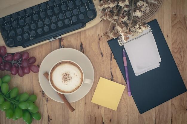 Máquinas de escribir vintage y taza de café en la mesa de madera.