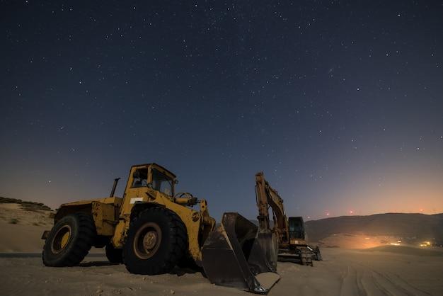 Máquinas de trabajo en una duna de arena del sur de españa por la noche.