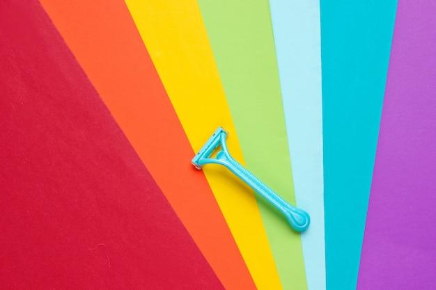 Maquinilla de afeitar para depilación sobre un fondo de color arcoíris