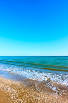 Mar, cielo azul y playa de arena - paisaje marino vertical. rimini, italia