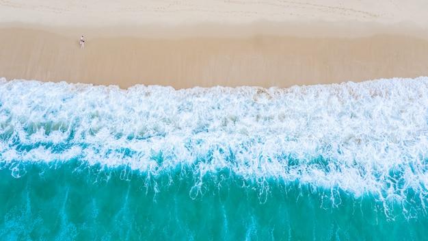 Mar esmeralda y pequeño turista en la playa de surin, phuket, tailandia