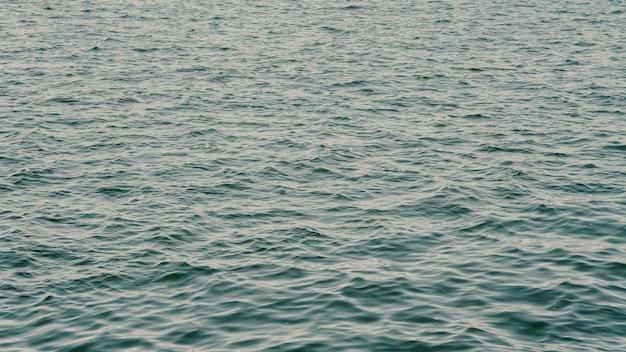Mar con hermosas olas y gotas de lluvia cayendo sobre la superficie