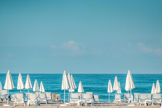 Mar de la mañana, playa, hamacas vacías para vacacionistas. concepto de vacaciones.