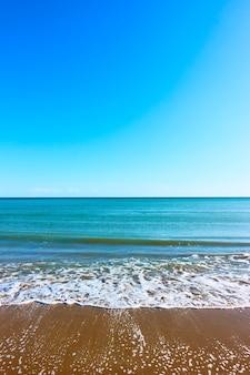 Mar y playa de arena: paisaje marino vertical con espacio para su propio texto, se puede utilizar como fondo
