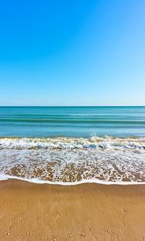 Mar y playa de arena. paisaje marino, vista vertical, fondo de pantalla para dispositivos móviles