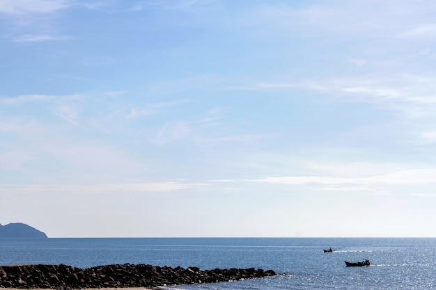 Mar y playa con barco de pesca en la mañana de verano