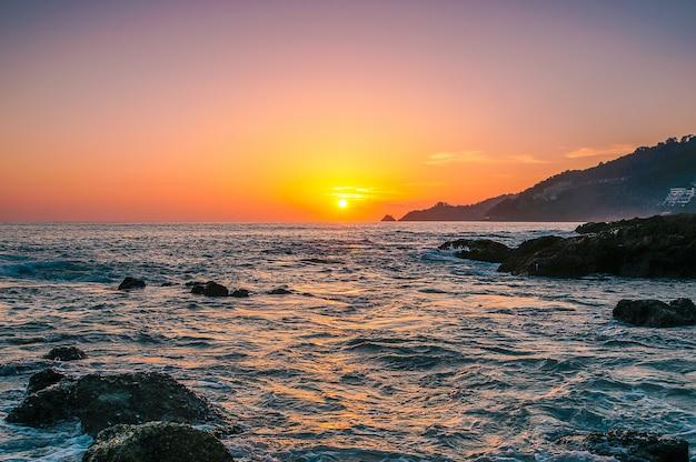 Mar puesta de sol o amanecer con colores de cielo y nubes en el crepúsculo