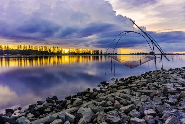 Mar puesta de sol o amanecer con herramienta de pesca campo y colorido del cielo en el crepúsculo