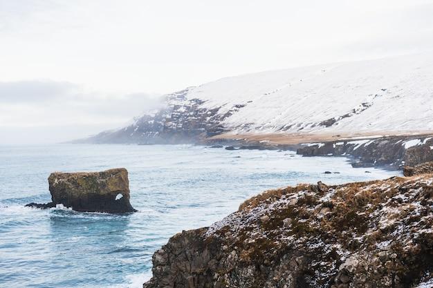Mar rodeado de colinas cubiertas de nieve y niebla bajo un cielo nublado en islandia