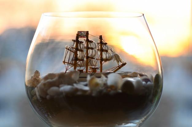 Mar viejo barco en una botella y una copa de vino.