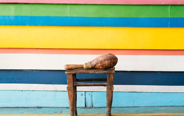 Maraca junto a una pared vibrante en rayas con espacio de copia