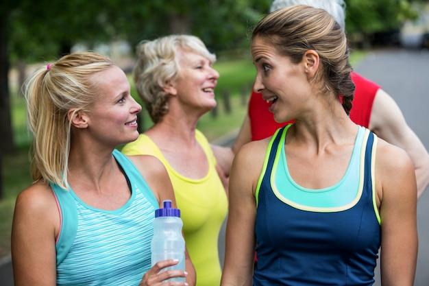 Maratón atleta femenina hablando y bebiendo agua