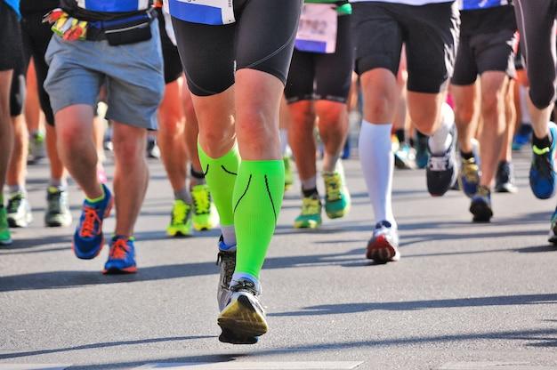Maratón carrera, pies de corredores en carretera, deporte, fitness y concepto de estilo de vida saludable