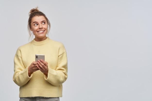Maravilla, mujer de aspecto feliz con cabello rubio recogido en un moño. vistiendo un suéter amarillo y sosteniendo un teléfono inteligente. mordiéndose el labio y mirando hacia la derecha en el espacio de la copia, aislado sobre una pared blanca