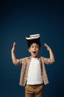 Maravilla del mundo real. niño o niño en jeans y camisa con gafas de casco de realidad virtual aisladas sobre fondo azul de estudio. concepto de tecnología de punta, videojuegos, innovación.