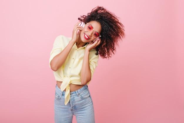 Maravillosa chica africana en jeans boyfriend relajante con música. retrato interior de mujer bonita mulata con peinado rizado viste camisa de algodón y pantalones de mezclilla.