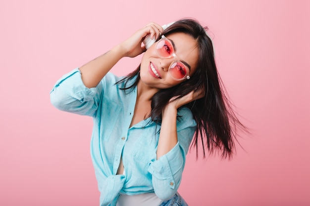Maravillosa chica asiática con expresión de cara feliz agitando el pelo mientras escucha música. linda modelo de mujer hispana escalofriante con su canción favorita.