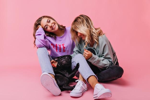 Maravillosa chica de cabello castaño en jeans divirtiéndose con cachorro de bulldog. extasiada mujer rubia jugando con su mascota con su mejor amiga.