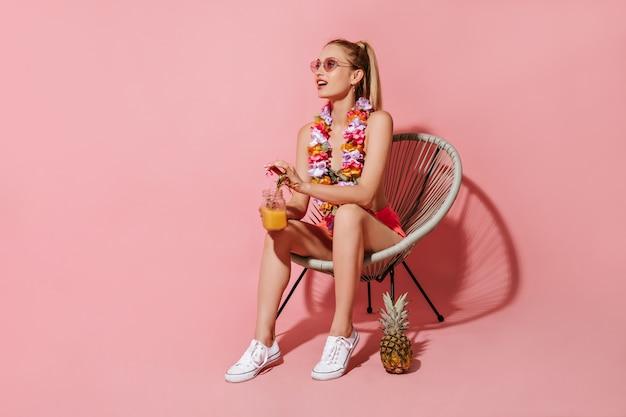 Maravillosa chica con cabello rubio en traje de baño, gafas de sol y collar de flores sentado en una silla y sosteniendo un cóctel en la pared rosa
