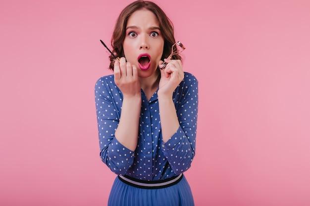 Maravillosa chica nerviosa con rimel y rizador de pestañas posando con la boca abierta. modelo femenino bien vestido conmocionado que se coloca en la pared rosada.