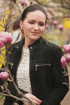 Maravillosa dama morena con maquillaje nude, vistiendo blusa de encaje, posando cerca de las flores de magnolia en flor