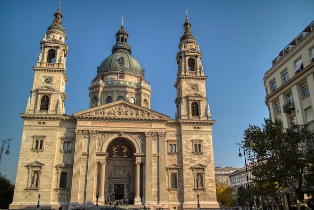 La maravillosa fachada de la basílica de san esteban es una catedral católica en budapest, hungría, sobre un fondo de cielo azul claro.