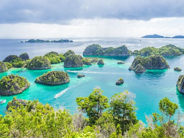 Maravillosa forma de isla, mar turquesa, lanchas rápidas y día nublado