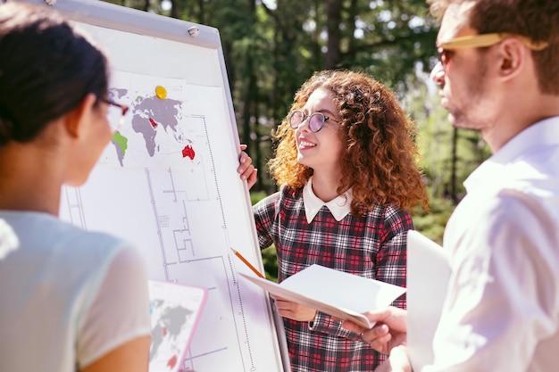 Maravillosa idea. alegre niña de pelo rizado presentando su proyecto y sus amigos escuchándola