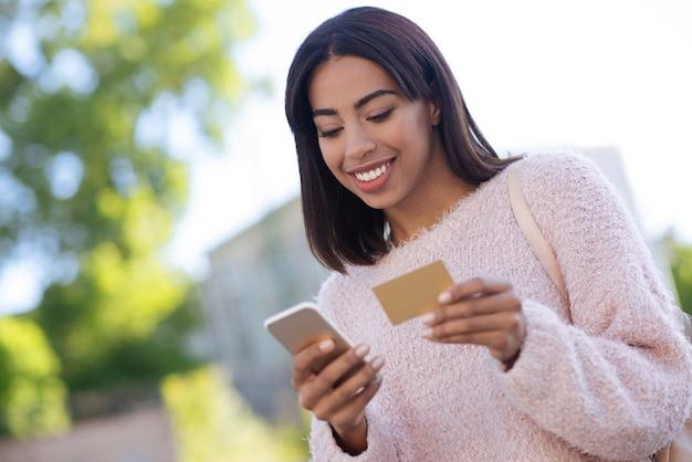 Maravillosa joven positiva comprando cosas en línea mientras usa su teléfono inteligente y su tarjeta de crédito