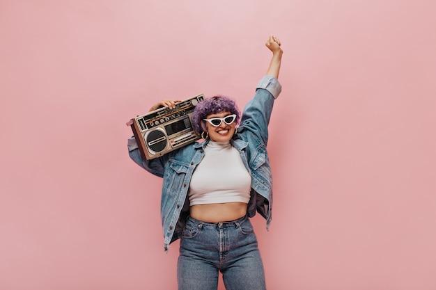 Maravillosa mujer alegre con corte de pelo corto de color púrpura con gafas de sol triangulares y aretes redondos divirtiéndose en rosa.