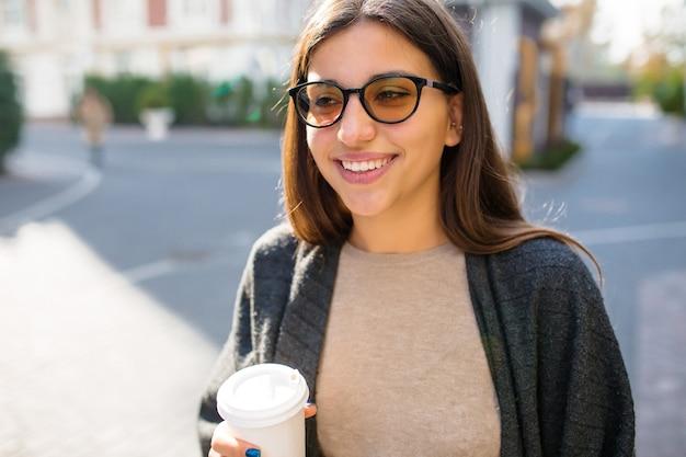 Maravillosa mujer elegante con gafas de sol y café para pasear por la calle