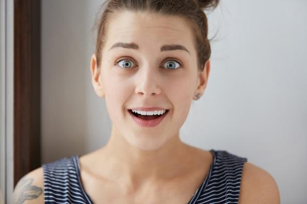 Maravillosa mujer europea con hermosos ojos azules y boca abierta. asombrosa expresión facial de una joven morena con tatuaje en el hombro. emociones de sorpresa.