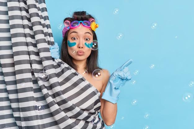 Maravillosa mujer hermosa con apariencia oriental disfruta de procedimiento de rutina matutino toma ducha en el baño en casa indica en espacio vacío en blanco hace peinado aislado sobre fondo azul.