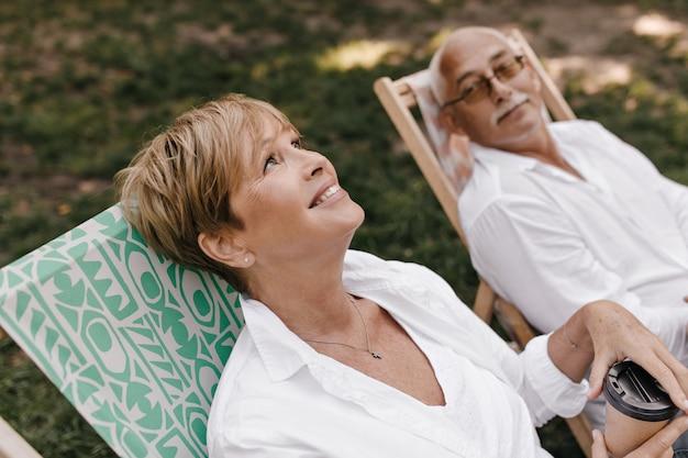 Maravillosa mujer de pelo rubio en ropa blanca sonriendo, sosteniendo una taza de té y sentada en una silla con un hombre de pelo gris con anteojos al aire libre.