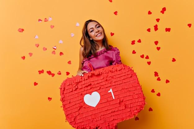 Maravillosa niña sonriente disfrutando de las redes sociales. retrato interior de glamorosa blogger femenina escalofriante en naranja.